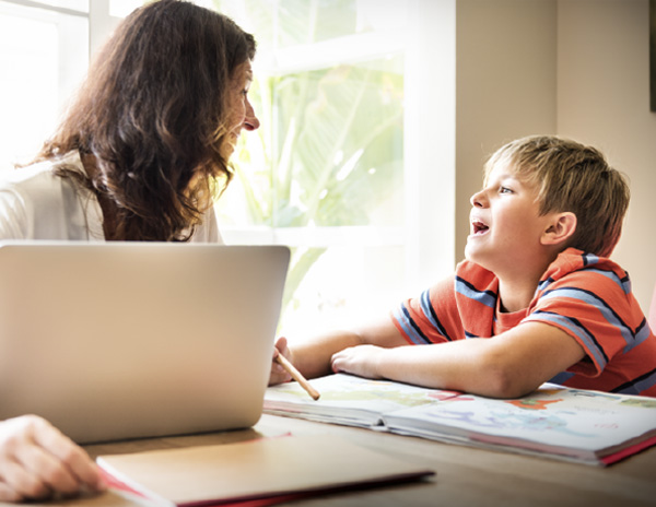 Male student working with hismother on a laptop at home