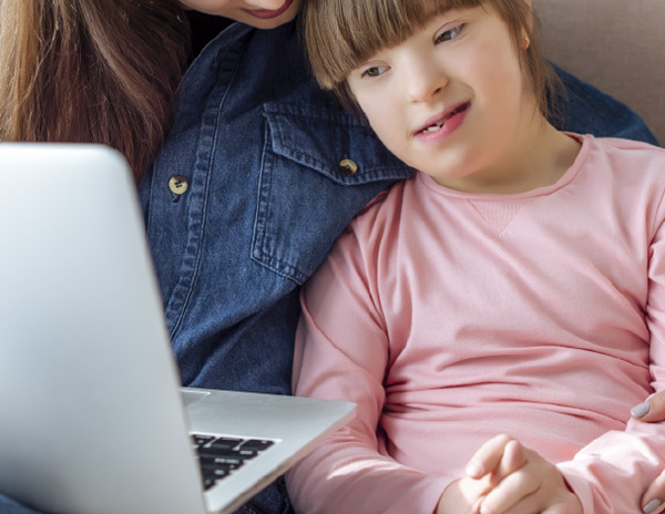 Female student sitting closelywith mother working on a laptop