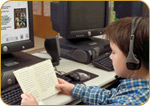 Young boy reads book while sitting at desk with headphones