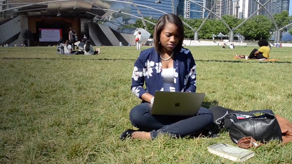 Pthara Jeppe sits in a park using her laptop.