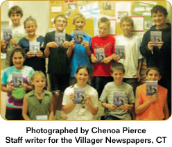 Group of twelve students smile holding up Don Johnston's Building Wings book