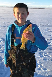 "alt=""Trei holds up a fish caught while ice-fishing""."