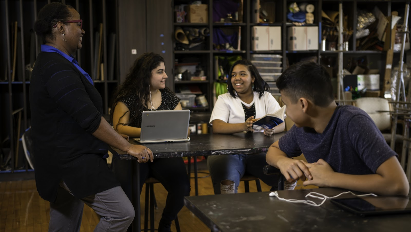 Three students interact with a teacher in a classroom