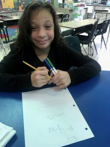 Student writing and smiling at the camera