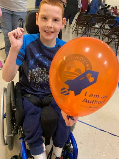 Student in a wheel chair holding a balloon that says I am an Author