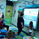 Students working at a smart board together