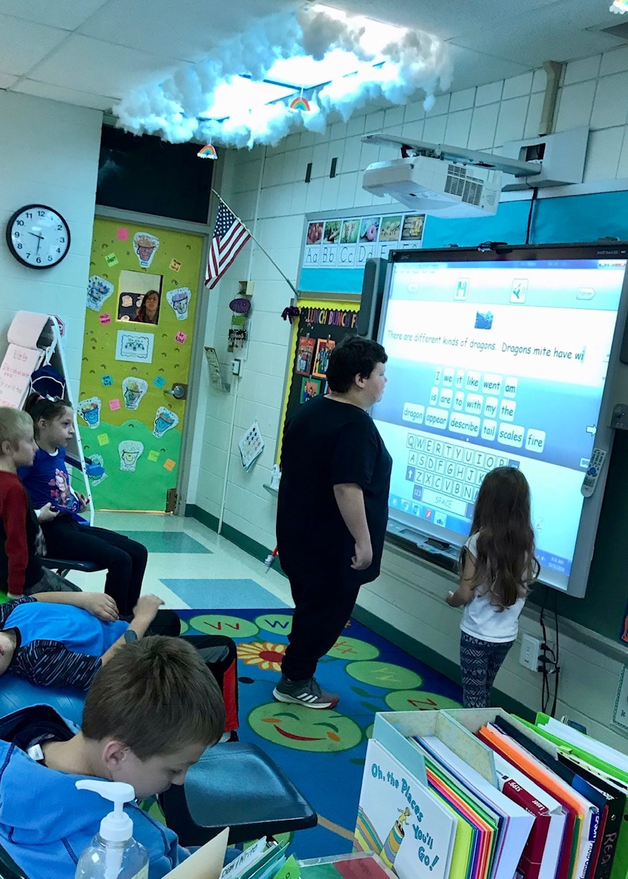 Students working at a smartboard together