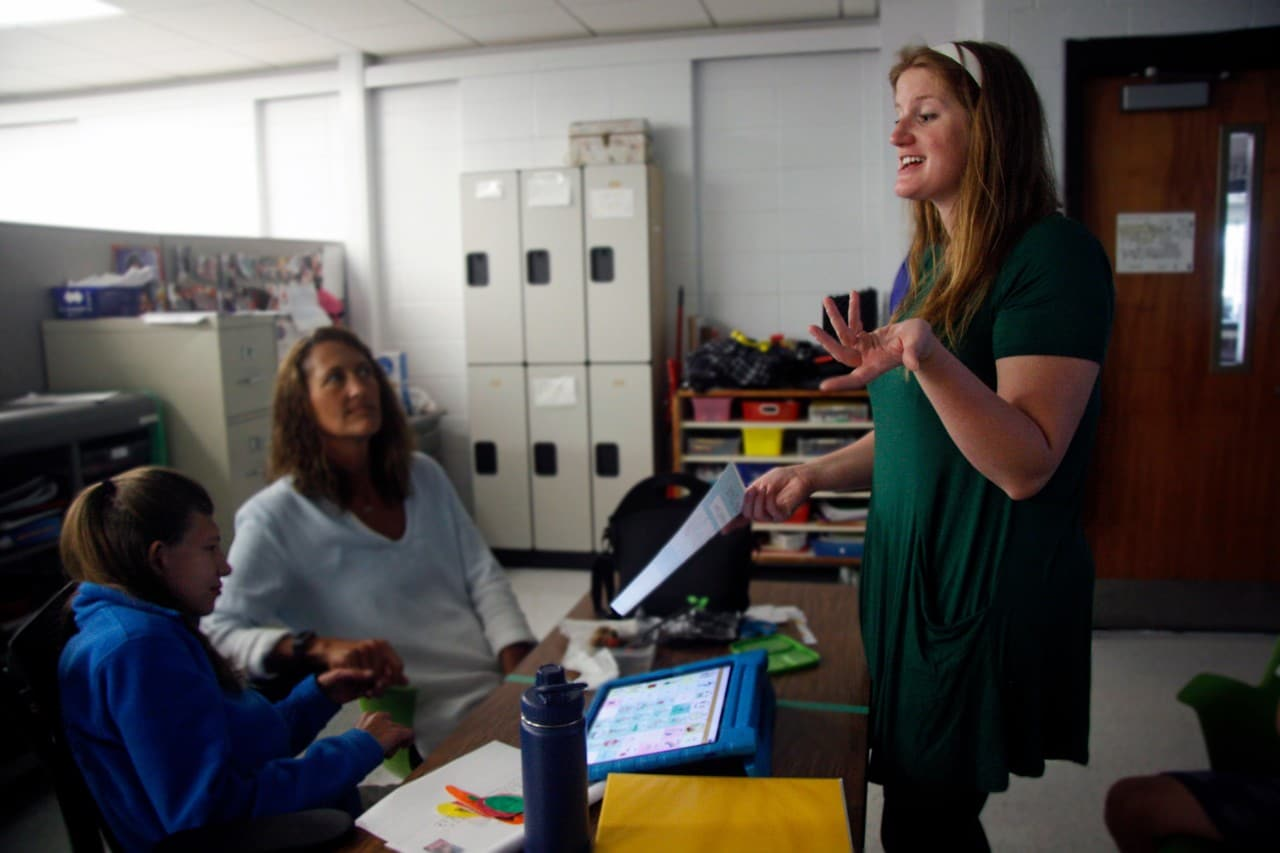 Abbey Lynch helping student with AAC device