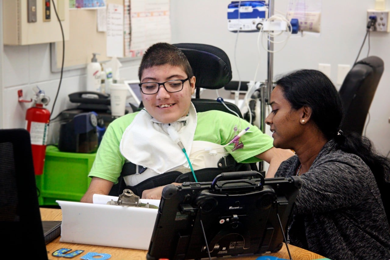 Student with AAC device smiling at helper