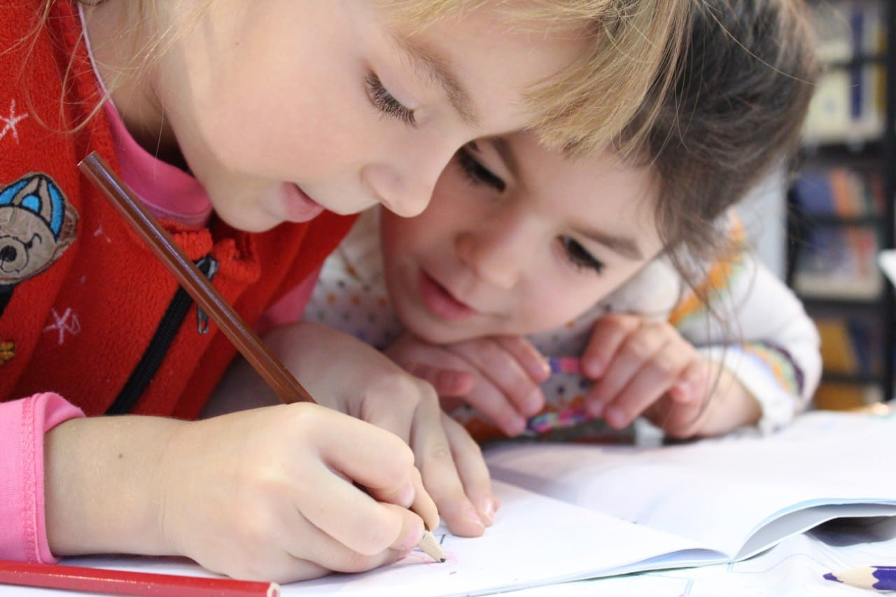 Two young girl students writing