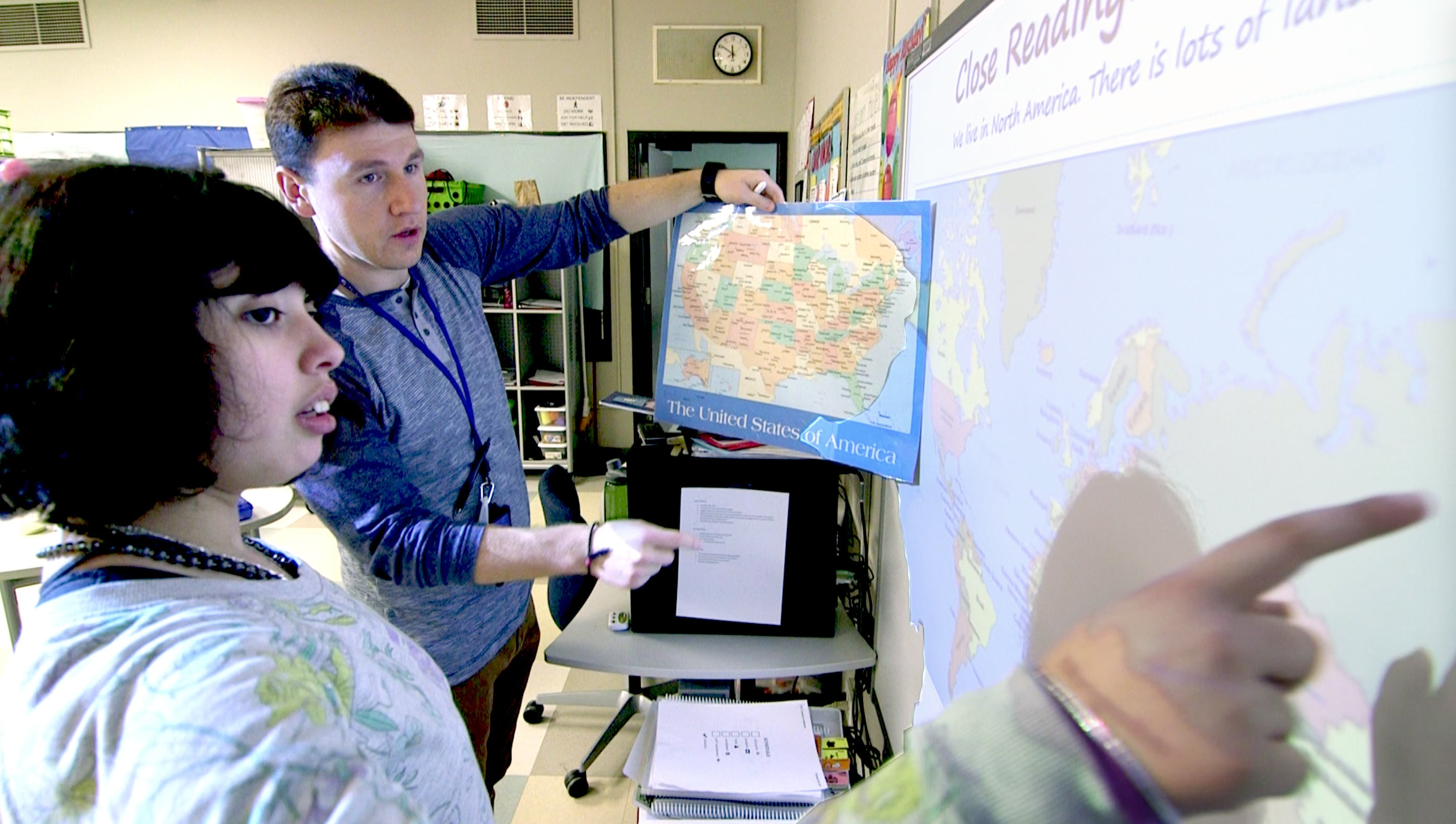 Erlind and a student comparing a map on the wall to a map in the lesson