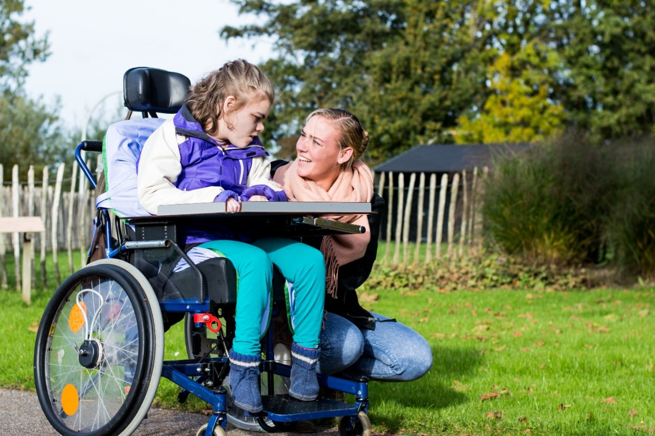 Girl in the wheel chair with teacher