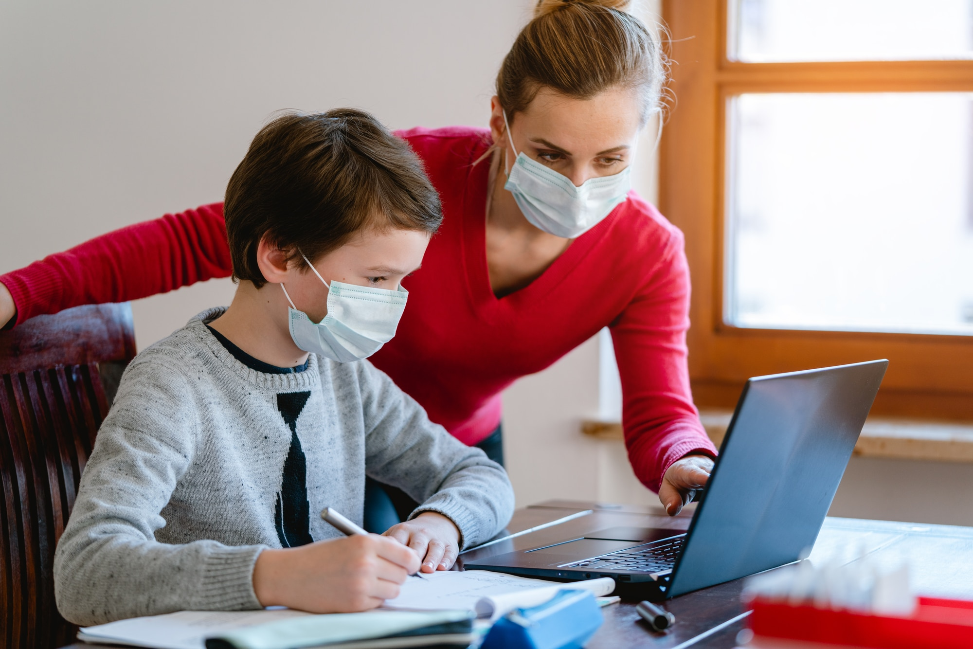 Student and teacher working together with masks on