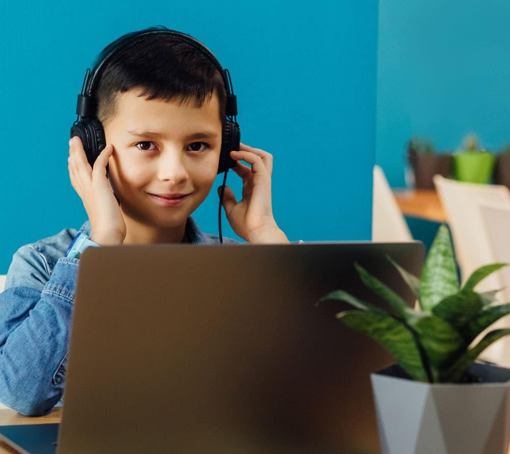Young boy on a laptop smiling with headphones on